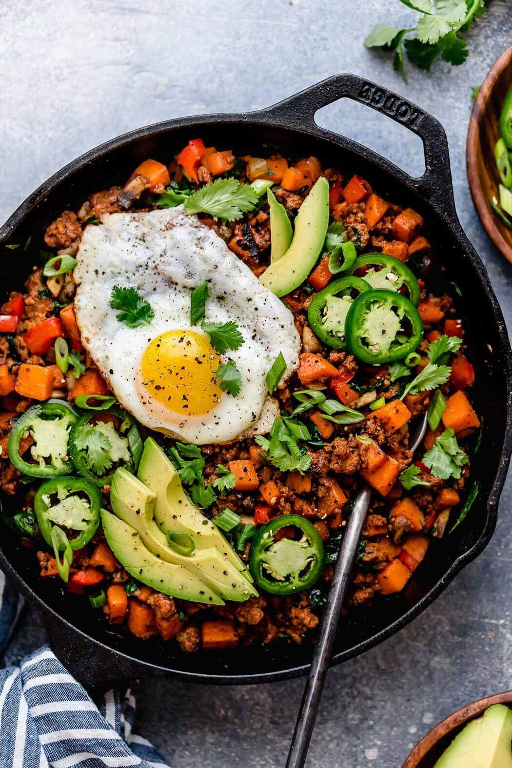 Tex-Mex Sweet Potato Hash in a black skillet with a serving spoon in it as well as a fried eggs, avocado slices, jalapeño slices, green onion and cilantro garnished over top.