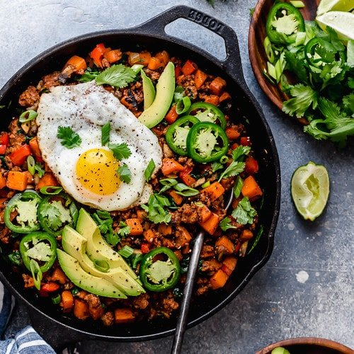 Sweet Potato Hash in a cast iron skillet and topped with a fried egg and avocado slices.