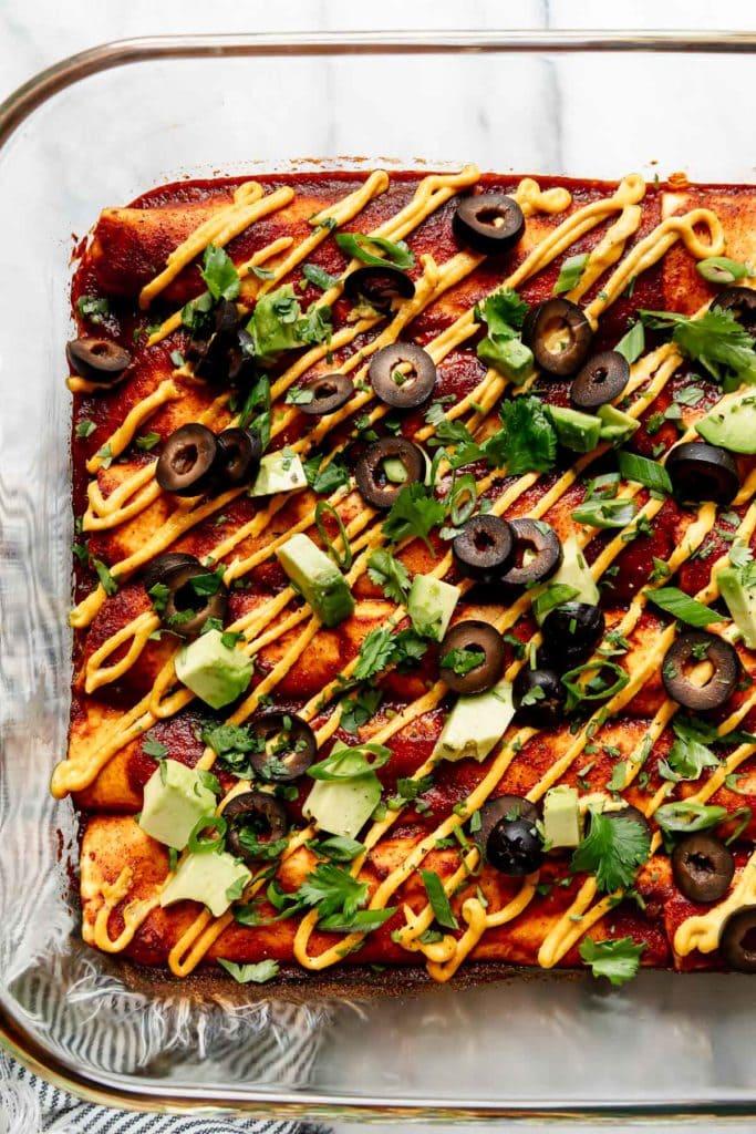 vegan enchiladas in a baking dish drizzled with vegan nacho cheese