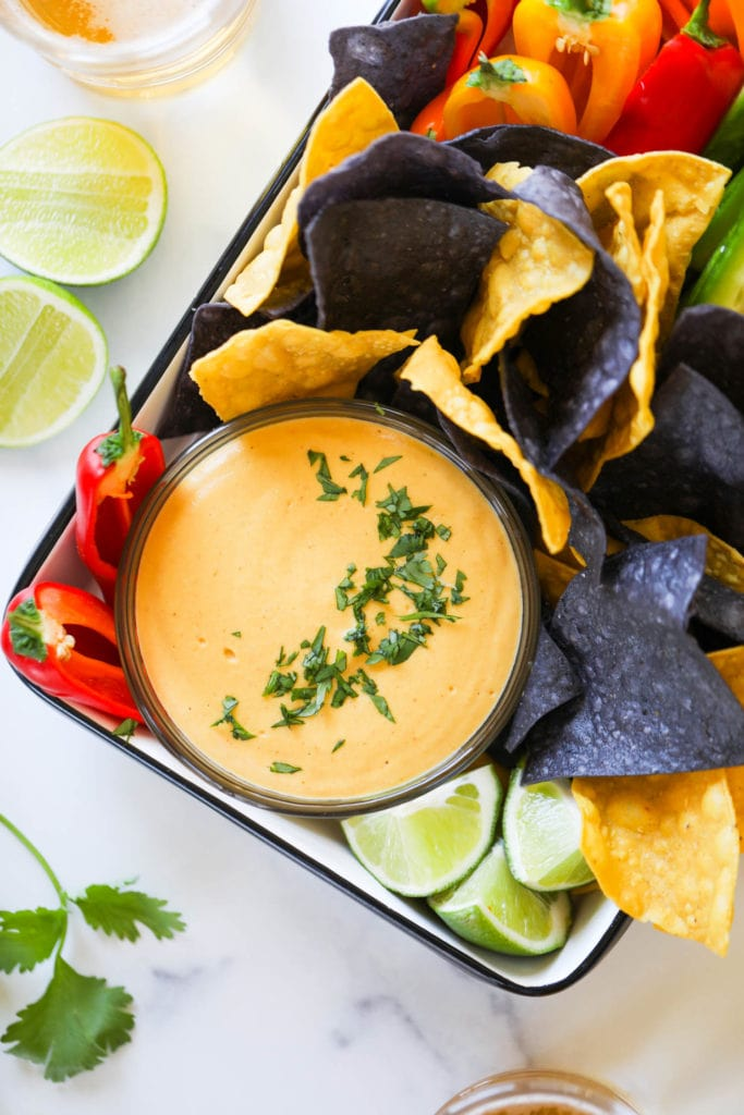 A black rimmed tray filled with vegan nacho cheese in a bowl surrounded with blue and yellow tortillas and fresh cut veggies