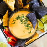 Creamy vegan nacho cheese in a small bowl surrounded with blue and yellow tortilla chips
