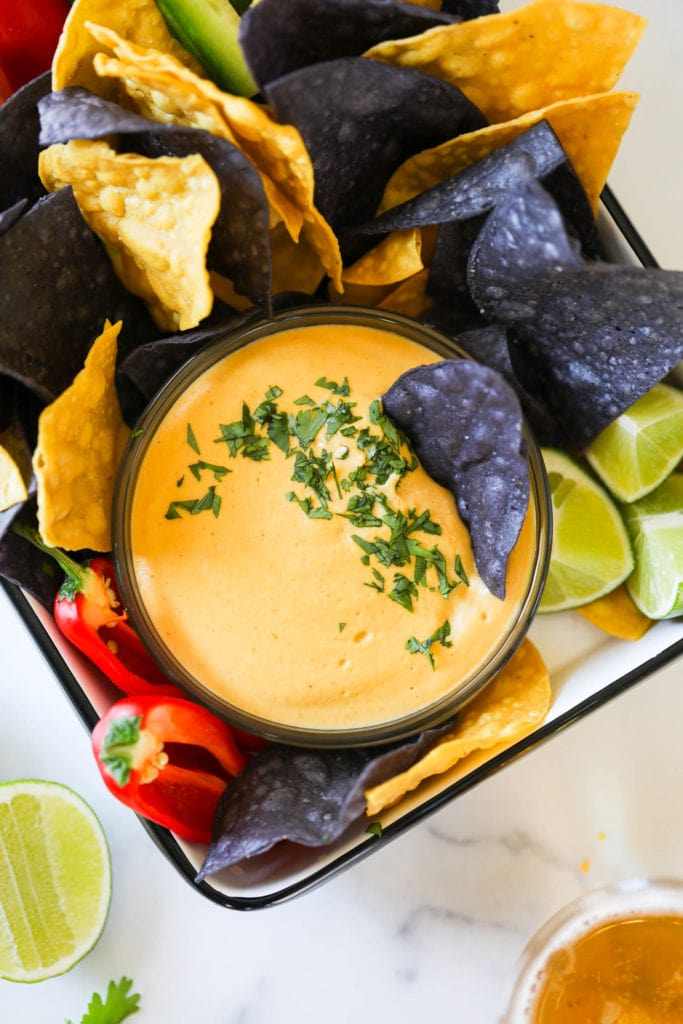 Vegan nacho cheese in a bowl sprinkled with fresh herbs surrounded with blue and yellow tortilla chips
