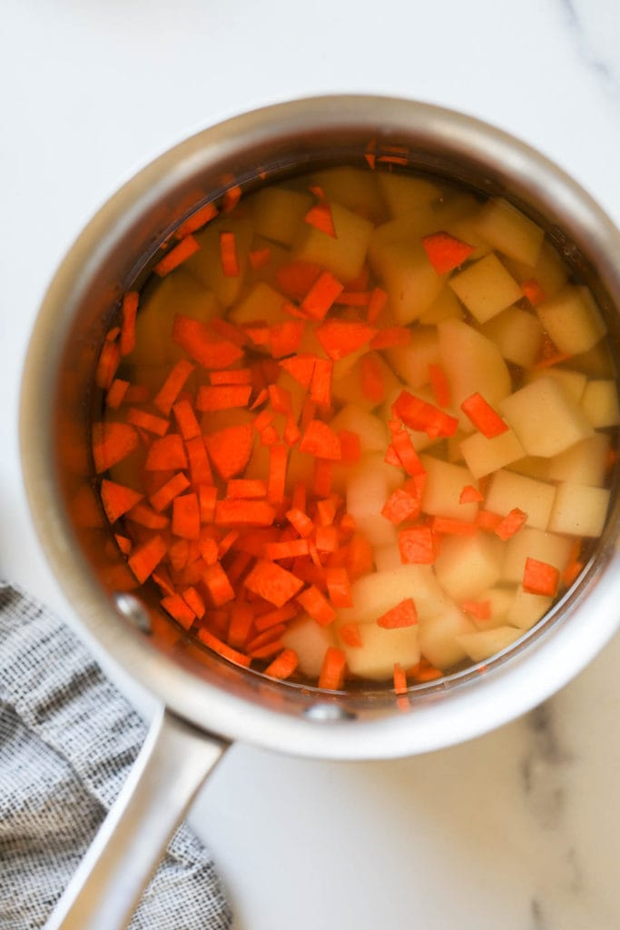 Yukon gold potatoes and cut carrots in a saucepan ready for boiling