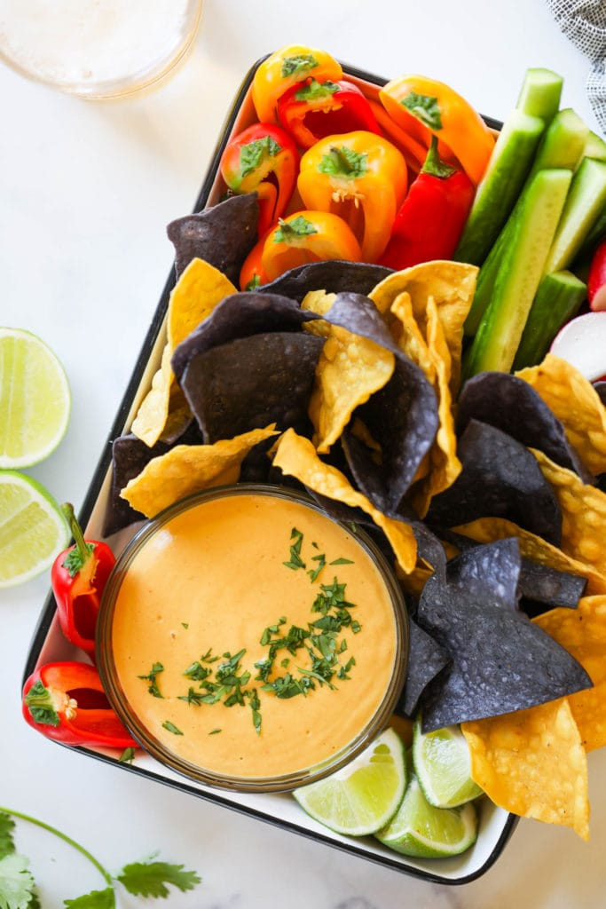 A tray filled with vegan nacho cheese in a bowl surrounded with blue and yellow tortilla chips and fresh cut veggies.
