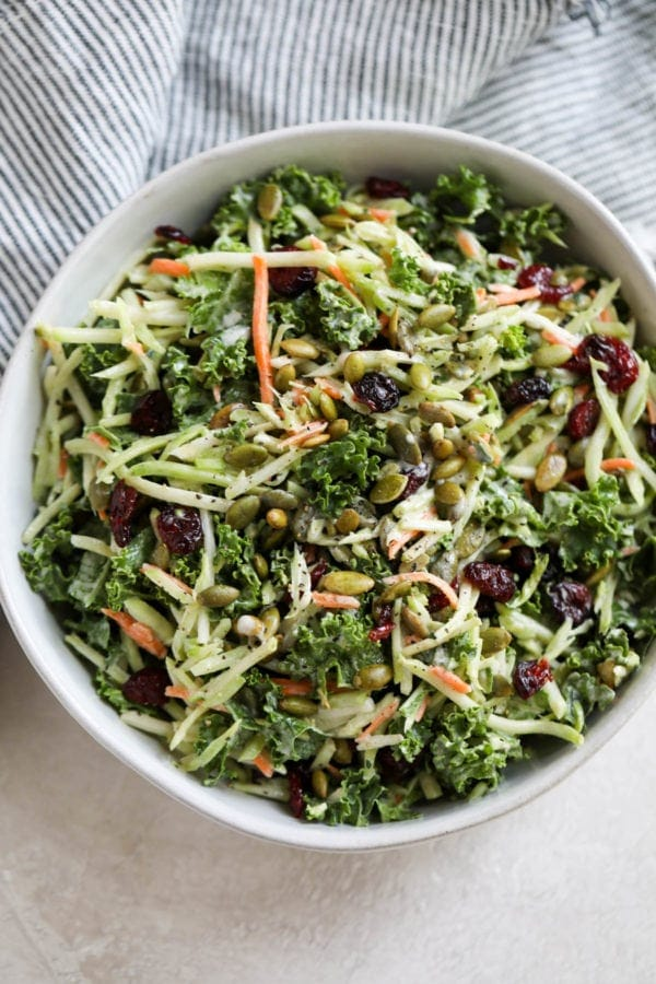 Creamy Gluten-free Broccoli Slaw with dried cranberries in a large white serving bowl.