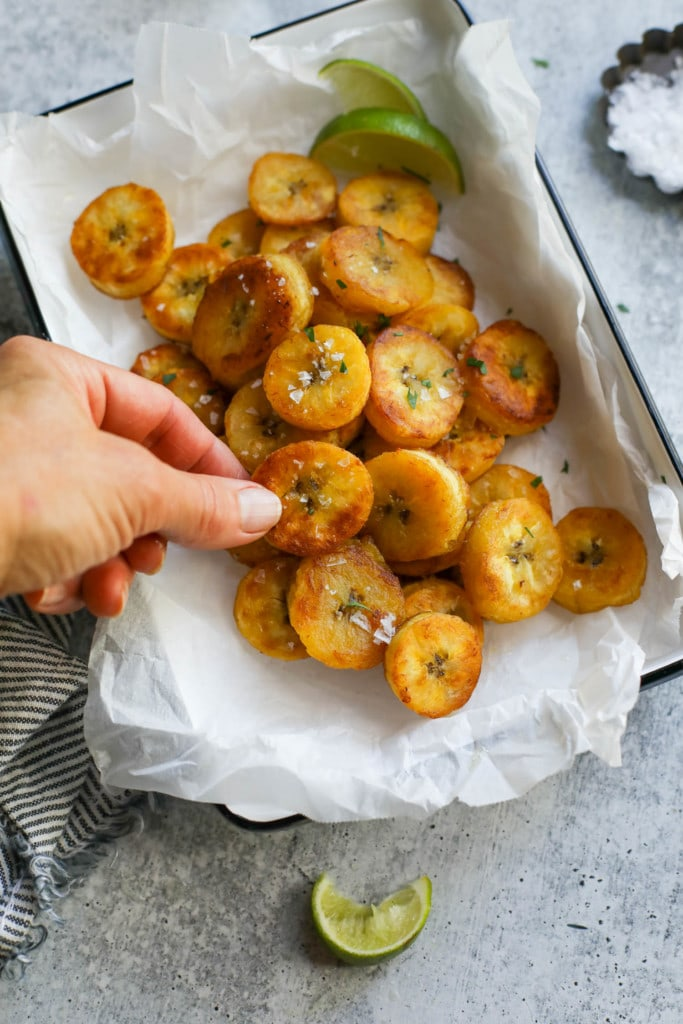 A pile of fried plantains with sea salt flakes sprinkled on top in a parchment-covered dish with one plantain round being picked up.