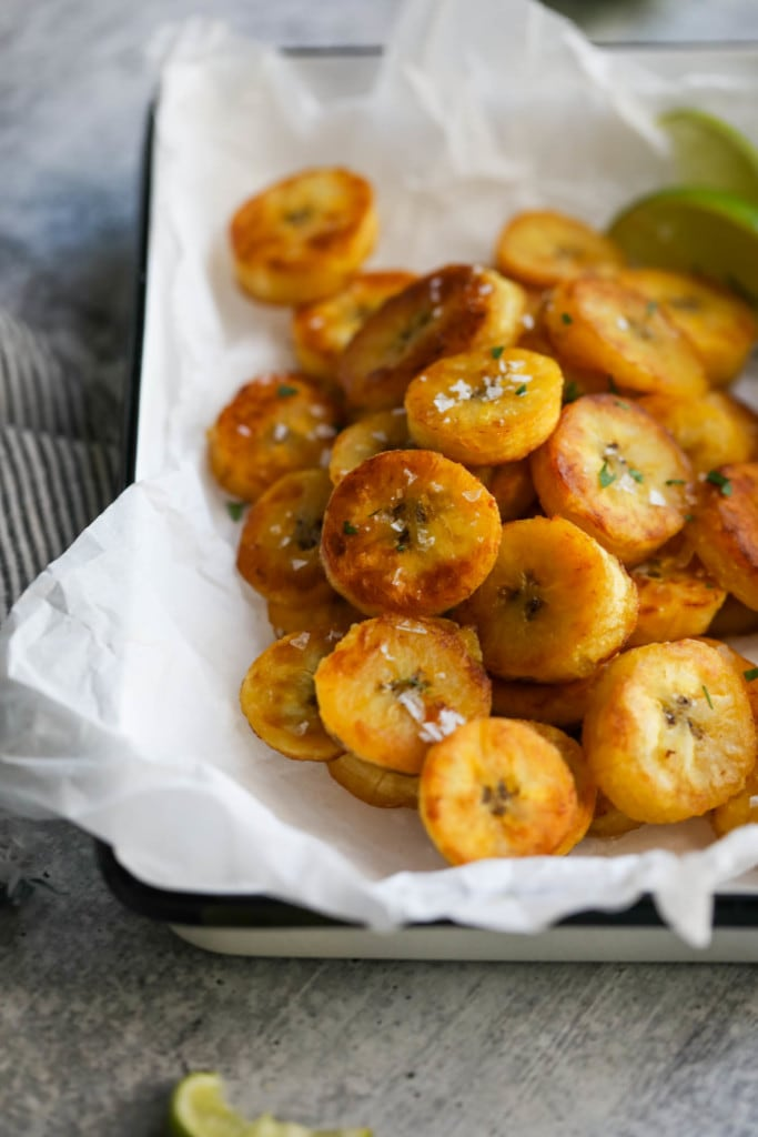 A close up of fried plantain rounds with sea salt flakes in a parchment-covered dish.