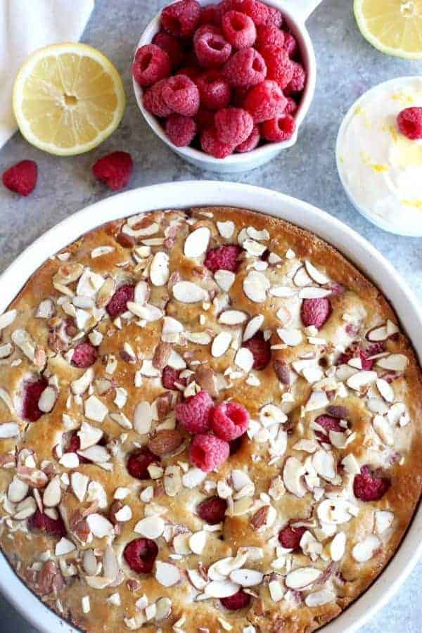 Gluten-free Raspberry Lemon Coffee Cake in a white pie dish with a side of raspberries