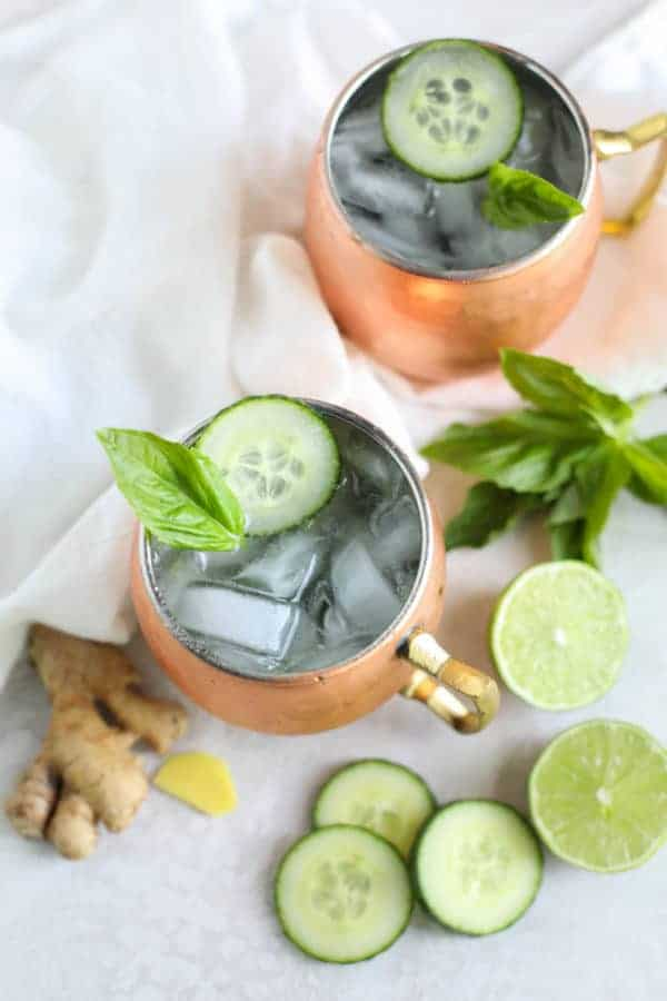Cucumber Basil Kombucha Mules in copper mugs with ingredients laying on the table