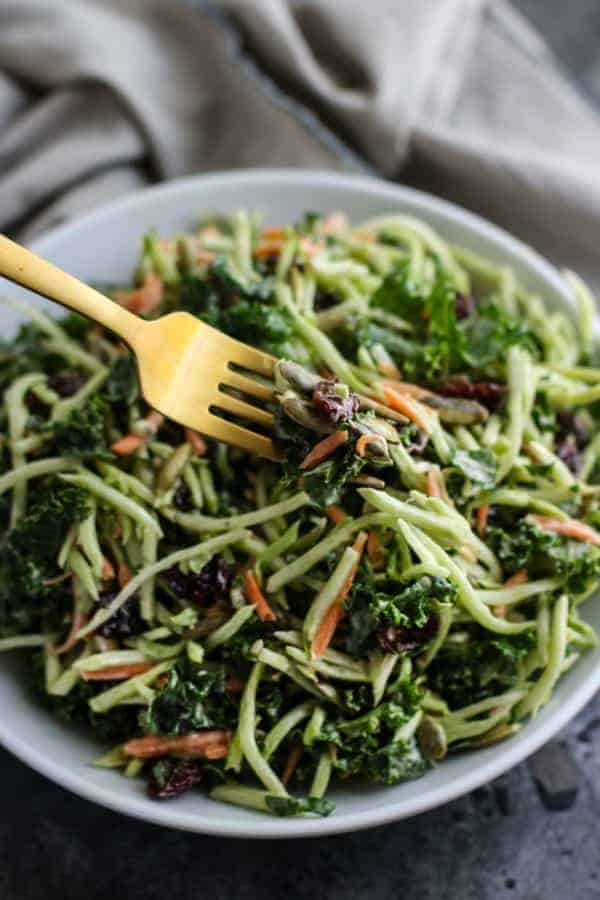 Creamy Broccoli Slaw on a golden fork and in a white bowl