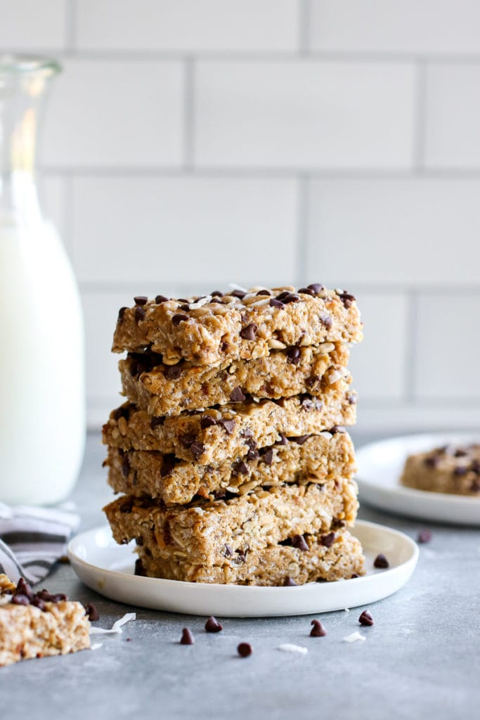 A tall stack of homemade chewy chocolate chip granola bars on a white plate