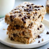Three homemade clif bars with chocolate chips and coconut stacked up on a white plate
