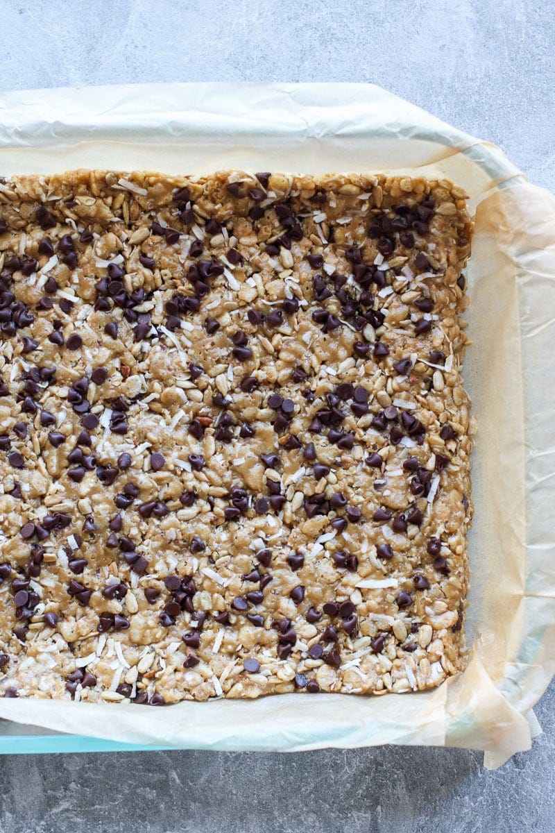 Soft and chewy chocolate chip granola bars pressed into a baking dish ready to cut into bars