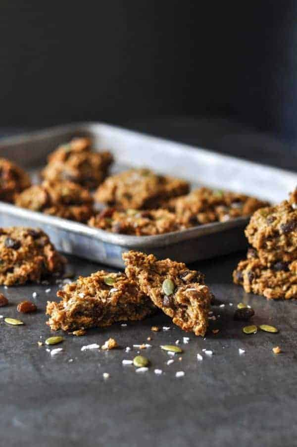 Two Gluten-free Pumpkin Breakfast Cookies on a table in front of a baking sheet with six cookies