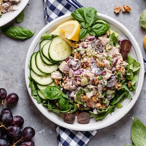Overhead view of creamy Waldorf chicken salad on a white plate over a bed of greens with grapes and cucumbers on the side.