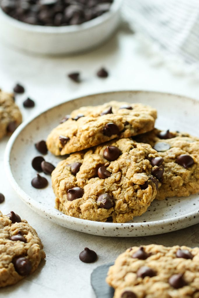 Three Healthy Peanut Butter Oatmeal Cookies with Chocolate Chips on a white speckled plate.