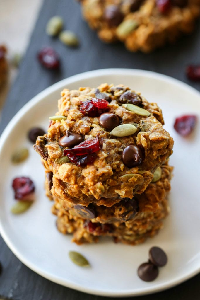 Healthy pumpkin breakfast cookies stacked up on a white plate with chocolate chips and dried cranberries on top.
