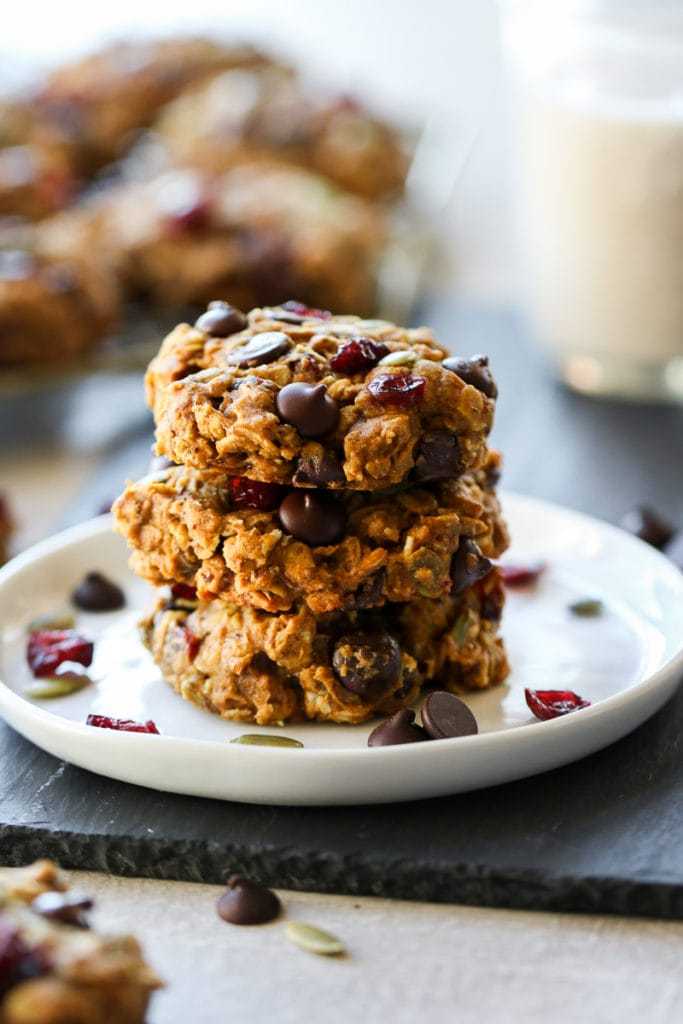 Three healthy oatmeal breakfast cookies stacked up on a white plate.
