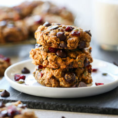 Three oatmeal pumpkin breakfast cookies stacked up on a white plate.