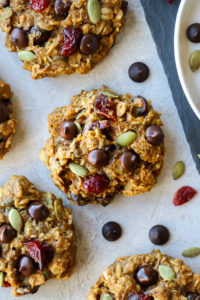 Close up view of pumpkin breakfast cookie topped with dark chocolate chips and dried cranberries.
