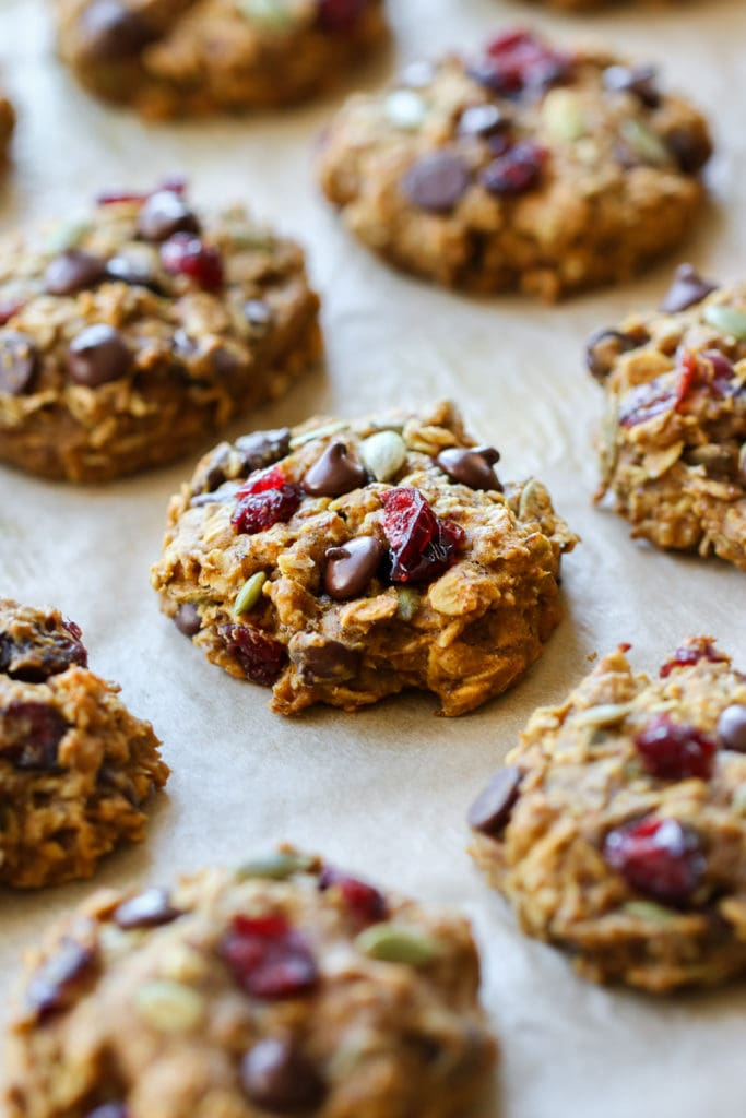 Perfectly baked pumpkin breakfast cookies with chocolate chips and cranberries on a parchment-covered baking sheet.