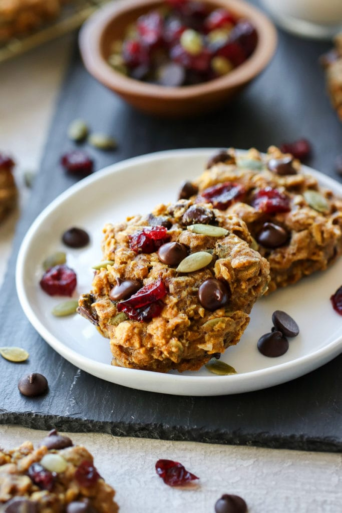 Two healthy pumpkin breakfast cookies studded with dark chocolate chips on a white plate.