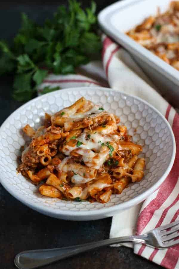baked ziti in a white bowl with fork