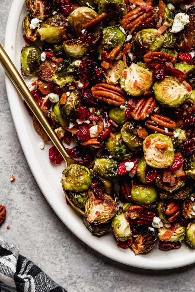 Roasted Brussel Sprouts with Bacon and Balsamic on a white serving platter with a gold serving spoon.