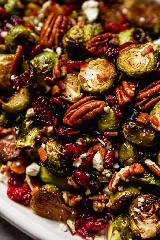 Roasted Brussel Sprouts with Bacon, pecans, cranberries and feta cheese on a white serving platter.