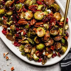 Roasted brussels sprouts with bacon and dried cranberries on a white serving platter