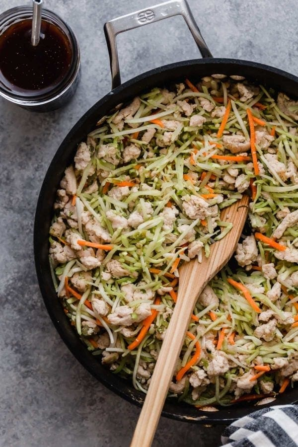 Egg roll in a bowl ingredients being stirred together in a large skillet with the sauce on the side