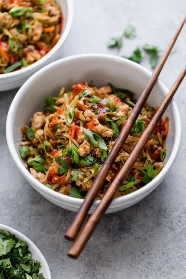 Egg roll in a bowl mixed together in a white bowl with chopsticks on the corner of the bowl