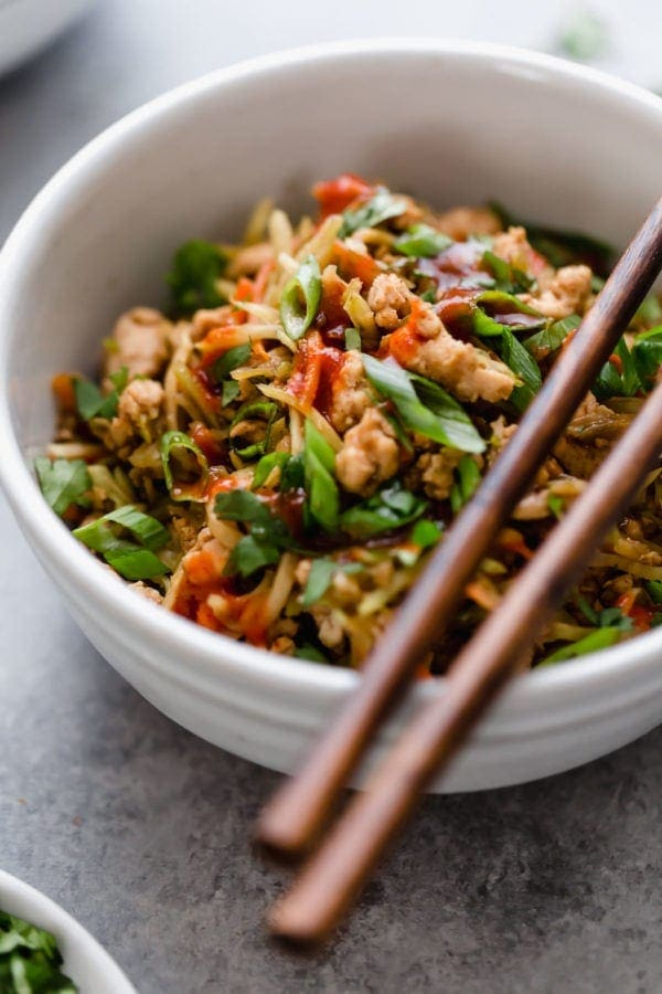 A close up view of Whole30 Egg Roll in a Bowl topped with scallions, carrot shreds, and sauce.