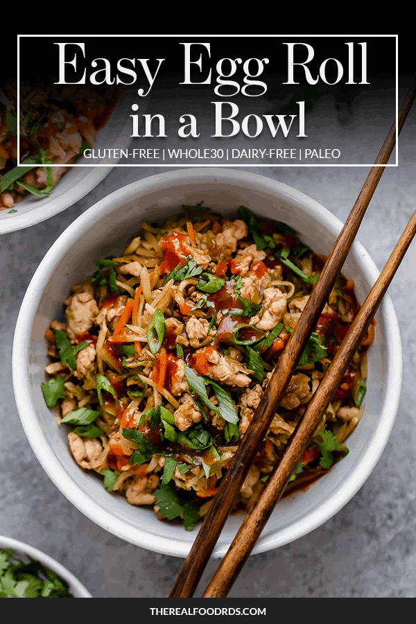 Easy egg roll in a bowl served in a white bowl topped with scallions and homemade sauce with chopsticks on the side