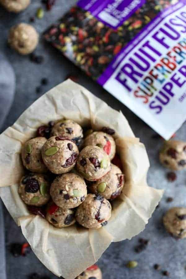 Bowl of energy bites next to a package of Made in Nature Fruit Fusion dried fruit mix.