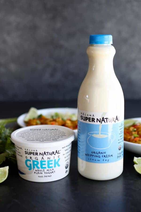 A container of Kalona SuperNatural Organic Greek Whole Milk Plain Yogurt next to a container of Kalona SuperNatural Organic Whipping Cream