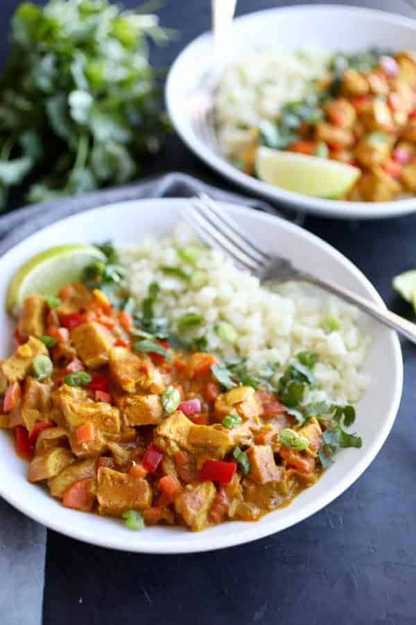 Indian Butter Chicken in a bowl served with cauliflower rice and topped with cilantro and green onions.