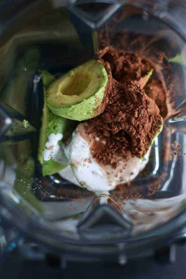 Avocados, cocoa powder and coconut milk in blender.