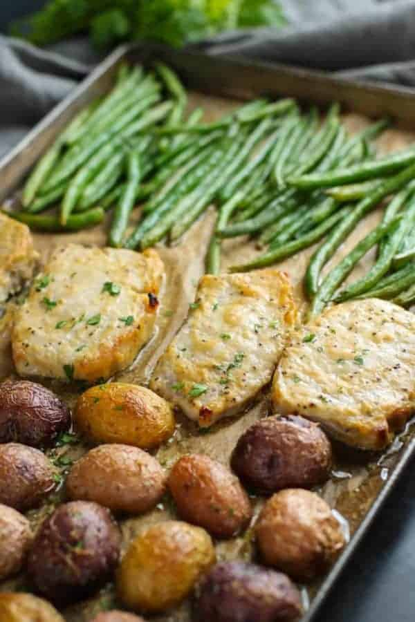 Sheet pan with pork chops, green beans and roasted potatoes.
