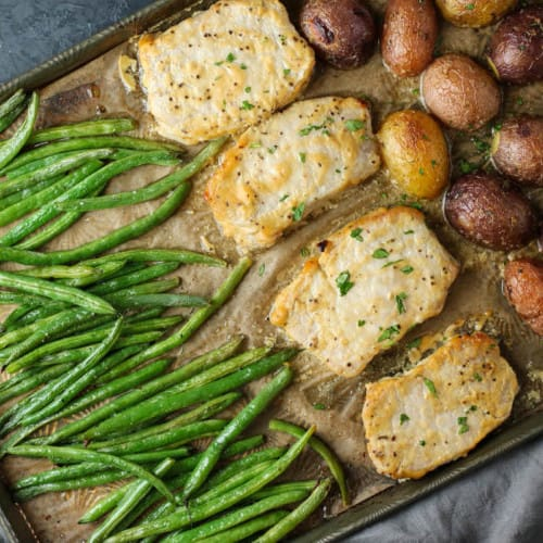 Overhead view of sheet plan meal that contains honey mustard-glazed porkchops, roasted green beans and potatoes.