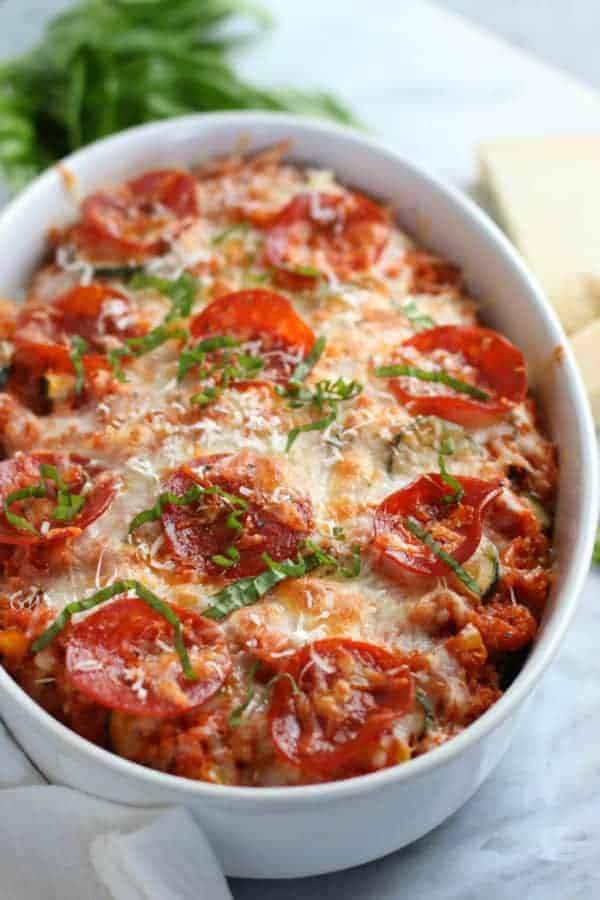 Close up of casserole dish with quinoa topped with melted cheese, pepperoni and fresh basil.