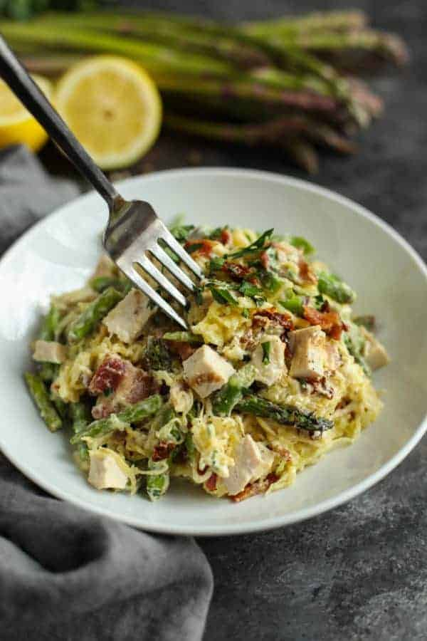 Creamy Chicken Spaghetti Squash with Bacon and Asparagus in a white bowl with a silver fork
