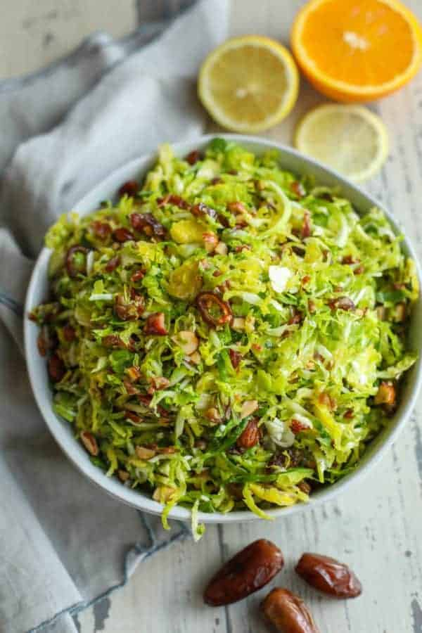 Sweet and Smoky Brussels Slaw in a bowl on a picnic table with dates and oranges on the side