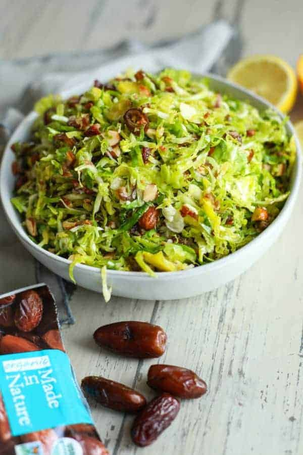 Brussels sprouts salad in a white bowl with package of Made in Nature pitted dates lying next to it.