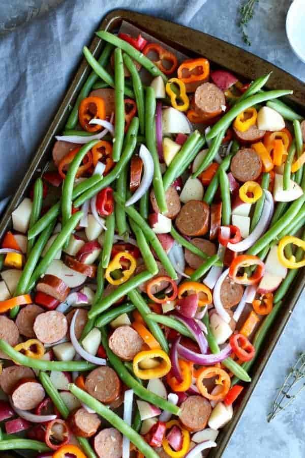 One-Pan Kielbasa Veggie Bake ingredients on a sheet pan