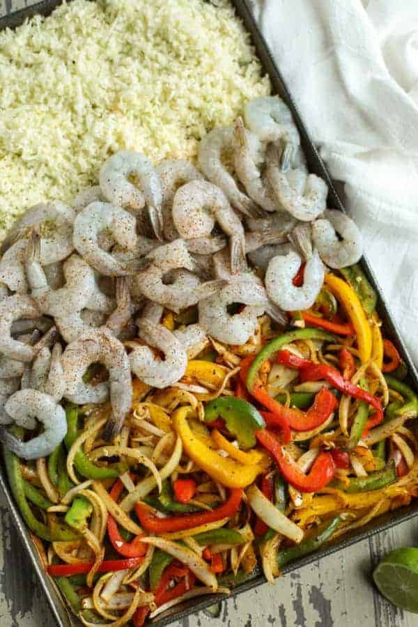 One-Pan Shrimp Fajita Bowls ingredients on a cookie sheet