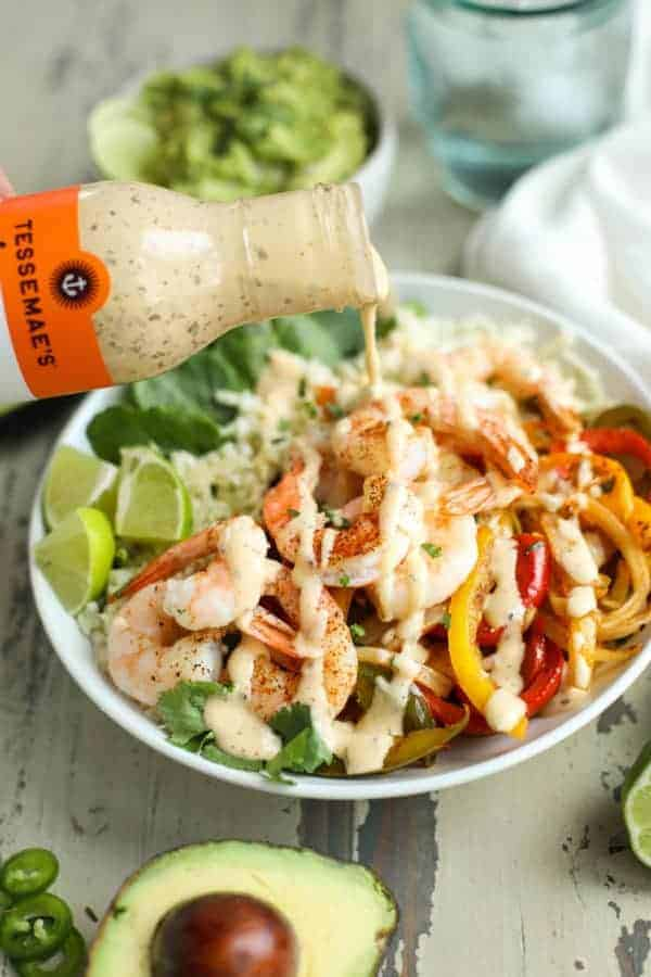 One-Pan Shrimp Fajita Bowl with Tessemae's dressing being poured over it