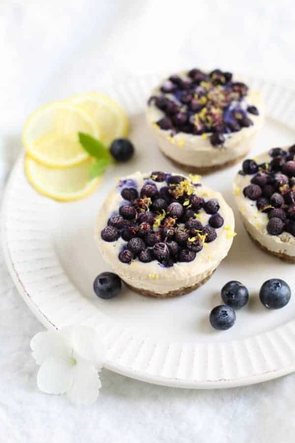 Vegan No-Bake Lemon Berry Mini Cheesecakes on a white plate with blueberries and lemons