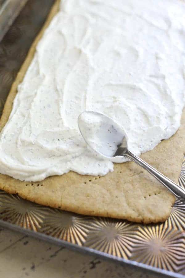 Sour cream being spread on a pizza crust