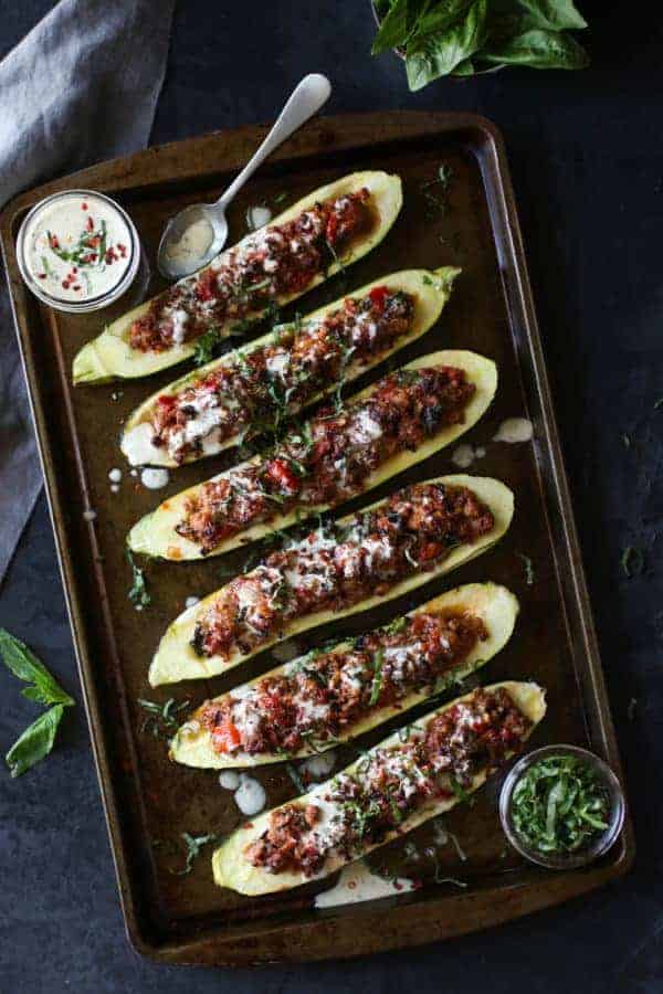 Italian-Sausage Stuffed Zucchini Boats with dressing and parsley on the side on a sheet pan